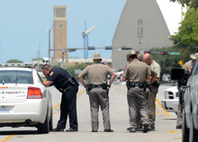 Texas State troopers and Brazos Valley lawmen work the scene of the shooting of two fellow law officers, Monday, Aug. 13, 2012 in College Station, Texas. Police say at least one law enforcement officer and one civilian have been killed in a shooting near Texas A&M University's campus. Assistant Chief Scott McCollum says the gunman also was shot Monday before being taken into custody.  (AP Photo/College Station Eagle, Dave McDermand)