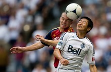 Real Salt Lake's Will Johnson, left, and Vancouver Whitecaps' Lee Young-Pyo, of South Korea, vie for the ball during the second half of an MLS soccer game in Vancouver, British Columbia, on Saturday, Aug. 11, 2012. (AP Photo/The Canadian Press, Darryl Dyck)