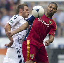 Vancouver Whitecaps' Jay DeMerit, left, and Real Salt Lake's Alvaro Saborio, of Costa Rica, vie for the ball during the first half of an MLS soccer game in Vancouver, British Columbia, on Saturday, Aug. 11, 2012. (AP Photo/The Canadian Press, Darryl Dyck)