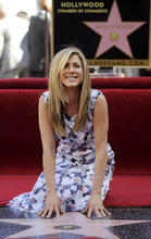 Actress Jennifer Aniston poses atop her new star on the Hollywood Walk of Fame in Los Angeles, Wednesday, Feb. 22, 2012. (AP Photo/Chris Pizzello)