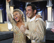 FILE - In this Nov. 26, 2007 file photo released by ABC, Helio Castroneves, right, and his partner Julianne Hough react to their scores by the judges after competing on the celebrity dance competition series