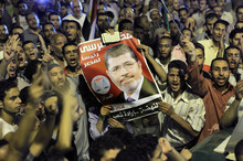 Thousands of supporters raise a poster of Egypt's Islamist President Mohammed Morsi as they celebrate in Tahrir Square, birthplace of the uprising that ousted Hosni Mubarak 18 months ago, in Cairo late Sunday, Aug. 12, 2012. Morsi ordered the retirement of the defense minister and chief of staff on Sunday and made the boldest move so far to seize back powers that the military stripped from his office right before he took over.  (AP Photo/Amr Nabil)