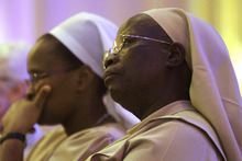 Sister Anne Nasimiyu, of Kenya, right, and Sister Lucy Marindany, of Milwaukee, Wis., join other members of The Leadership Conference of Women Religious (LCWR) at their national meeting Thursday, Aug. 9, 2012 in St. Louis.  The LCWR, the largest U.S. group for Roman Catholic nuns ,are meeting to decide how they should respond to a Vatican rebuke and order for reform. The LCWR represents about 80 percent of the 57,000 U.S. sisters. (AP Photo/Seth Perlman)