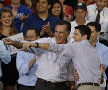 Republican presidential candidate Mitt Romney, left,  and his vice presidential running mate Rep. Paul Ryan, R-Wis, point to people in the crowd at a welcome home rally Sunday, Aug. 12, 2012 in Waukesha, Wis. (AP Photo/Jeffrey Phelps)