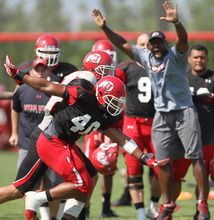 Lennie Mahler  |  The Salt Lake Tribune Utes cornerbacks coach Sharrieff Shah cheers as Utah linebacker Jacoby Hale stops QB Travis Wilson's rush in a practice scrimmage Saturday, Aug. 11, 2012.
