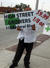 A sign-spinner outside a west Denver medical marijuana dispensary advertises low-cost pot as rush hour drivers pass the pot shop on Monday, Aug. 13, 2012. The spinner, who wouldn't give his name, could be out of a job under an outdoor advertising ban was approved by the Denver City Council. (AP Photo/Kristen Wyatt)