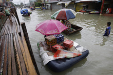 Residents use makeshift floats as others cross a makeshift bridge built over a flooded road in suburban Pasig, east of Manila, Philippines, Wednesday Aug. 15, 2012. A second tropical storm in as many weeks battered the northern Philippines on Wednesday as forecasters warned that the still-reeling capital could see more flooding. (AP Photo/Aaron Favila)
