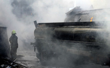In this photo released by the Syrian official news agency SANA, a firefighter extinguishes fire at the scene after a bomb attached to a fuel truck exploded outside a Damascus hotel where U.N. observers are staying according to the Syria's state TV  in Damascus, Syria, Wednesday Aug. 15, 2012. According to an Associated Press reporter at the scene, the blast had gone off inside a different parking lot, one belonging to a military compound and not the military command. The lot is near the Dama Rose Hotel, popular with the U.N. observers in Syria. (AP Photo/SANA)