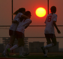 Steve Griffin | The Salt Lake Tribune   Judges Madison Ulibarri, Marissa Ulibarri and Alix Margolis celebrate a goal as the sun glows on the horizon during soccer game between Judge and Highland at Judge Memorial Catholic High School in Salt Lake City, Utah Tuesday August 14, 2012.