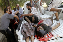 Dead and injured Syrians arrive at a field hospital after an air strike hit their homes in the town of Azaz on the outskirts of Aleppo, Syria, Wednesday, Aug. 15, 2012. (AP Photo/Khalil Hamra)
