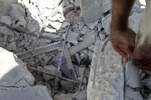 An arm of a dead Syrian woman peeks from the rubble of her destroyed house after an air strike destroyed at least ten houses in the town of Azaz on the outskirts of Aleppo, Syria, Wednesday, Aug. 15, 2012. (AP Photo/ Khalil Hamra)