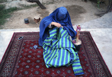 An Afghan tailor woman clad in a burqa sews a gown in Mazar-i-Sharif, north of Kabul, Afghanistan, Thursday, Aug. 16, 2012. (AP Photo/Mustafa Najafizdada)