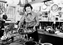 In this Aug. 21, 1978, file photo, American television chef Julia Child shows a salade nicoise she prepared in the kitchen of her vacation home in Grasse, southern France. Child, who changed the way Americans look at food as well as the way women looked at cooking and themselves, would have been 100 on Aug. 15. (AP Photo, File)