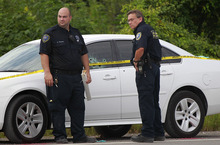 St. John the Baptist Parish Sheriff deputies examine a car with bullet holes at a crime scene where two sheriffs were killed and two wounded in an early morning shootout in St. John the Baptist Parish, west of New Orleans, Thursday, Aug. 16, 2012. (AP Photo/Gerald Herbert)