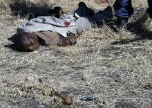 EDS NOTE GRAPHIC CONTENT: The body of a man lays in a mining area between Brits and Rustenburg, South Africa, Monday, Aug. 13, 2012.  Police say that  9 people, including 2 officers, have been killed in killed in ongoing violent mine protests. (AP Photo/ Leon Nicholas-STAR Business Report) SOUTH AFRCA OUT. CREDIT MANDATORY