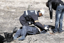 An injured policeman is attended to after he was attacked and injured by striking Lonmin miners near Rustenburg, South Africa, Monday, Aug. 13, 2012.  Police say that 9 people, including 2 officers, have been killed in ongoing violent mine protests. (AP Photo/ Leon Nicholas-STAR Business Report) SOUTH AFRCA OUT. CREDIT MANDATORY