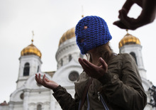 An unidentified supporter of Pussy Riot speaks to the assembled press outside the Christ the Saviour Cathedral, in Moscow, Wednesday, Aug. 15, 2012. The global campaign to free Pussy Riot is gaining speed: Supporters of the punk provocateur band mobilize this week in at least a two dozen cities worldwide to hold simultaneous demonstrations an hour before a Russian court rules on whether its members will be sent to prison. (AP Photo/Alexander Zemlianichenko)