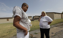 Twelve-year-old Elijah Earnheart, left, looks on as his mom Cindy Earnheart takes a phone call from his football coach outside his home in Mesquite, Texas, Thursday, Aug. 16, 2012.  The 6-foot, 300-pound 12-year-old has been ruled ineligible to play Pee Wee football in the Dallas area. Despite being a young seventh-grader, officials say is more than twice the maximum allowable Pee Wee weight of 135 pounds. (AP Photo/LM Otero)