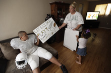 Cindy Earnheart, right, shows a sign she made for her son twelve-year-old Elijah Earnheart, left, as her three year old daughter Larnai tugs at their home in Mesquite, Texas, Thursday, Aug. 16, 2012. The 6-foot, 300-pound 12-year-old has been ruled ineligible to play Pee Wee football in the Dallas area. Despite being a young seventh-grader, officials say is more than twice the maximum allowable Pee Wee weight of 135 pounds. (AP Photo/LM Otero)