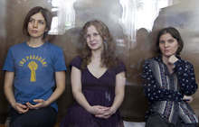 FILE In this Wednesday, Aug. 8, 2012 file photo feminist punk group Pussy Riot members, from left, Nadezhda Tolokonnikova, Maria Alekhina and Yekaterina Samutsevich sit in a glass cage at a court room  in Moscow, Russia. Three members of Pussy Riot were jailed in March and charged with hooliganism motivated by religious hatred after their punk performance against President Putin in Moscow's main cathedral.  (AP Photo/Misha Japaridze, file)
