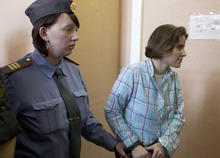 Yekaterina Samutsevich, right, a member of feminist punk group Pussy Riot is excorted to a court room in Moscow, Russia, Friday, Aug. 17, 2012.  Security is tight around a Moscow courthouse where three members of the feminist punk band Pussy Riot are to hear the verdict Friday in a trial that could send them to prison for seven years. (AP Photo/Misha Japaridze)