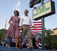 President Barack Obama and first lady Michelle Obama arrive at a campaign event, Wednesday, Aug. 15, 2012, in Davenport, Iowa,  during a three day campaign bus tour through Iowa. (AP Photo/Carolyn Kaster)