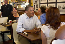 President Barack Obama has breakfast with three Iowa veterans, Amanda Irish, Jake Krapfi and Terry Phillips at Riley's Cafe and Catering, Wednesday, Aug. 15, 2012, in Cedar Rapids, Iowa,  during a three day campaign bus tour through Iowa. (AP Photo/Carolyn Kaster)