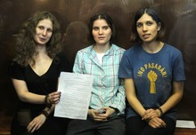 Feminist punk group Pussy Riot members, from left, Maria Alekhina, Yekaterina Samutsevich, and Nadezhda Tolokonnikova show the court's verdict as they sit in a glass cage at a court room in Moscow, Russia on Friday, Aug 17, 2012. A judge found three members of the provocative punk band Pussy Riot guilty of hooliganism on Friday, in a case that has drawn widespread international condemnation as an emblem of Russia's intolerance of dissent. (AP Photo/Mikhail Metzel)