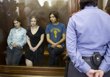 Feminist punk group Pussy Riot members, Nadezhda Tolokonnikova, right, Maria Alekhina, center, and Yekaterina Samutsevich, sit in a glass cage at a court room in Moscow, Russia, Friday, Aug. 17, 2012.  The three women in the band have been in jail for more than five months because of a prank they carried out in Moscow's main cathedral in a demonstration against Russia's Vladimir Putin, and they now face a maximum seven years in jail. (AP Photo/Misha Japaridze)