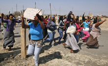 Women protest against the police near the scene of the shooting of miners Thursday at the Lonmin mine near Rustenburg, South Africa, Friday, Aug. 17, 2012. Frantic wives searched for missing loved ones, President Jacob Zuma rushed home from a regional summit and some miners vowed a fight to the death Friday as police finally announced the toll from the previous day's shooting by officers of striking miners: 34 dead and 78 wounded. Placard reads: 'Come Zuma'.  (AP Photo/Themba Hadebe)