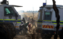 Striking mineworkers throw stones as police open fire on striking miners at the Lonmin Platinum Mine near Rustenburg, South Africa, Thursday, Aug. 16, 2012. South African police opened fire Thursday on a crowd of striking workers at a platinum mine, leaving an unknown number of people injured and possibly dead. Motionless bodies lay on the ground in pools of blood. (AP Photo)