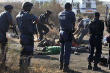 Police surround the bodies of striking miners after opening fire on a crowd  at the Lonmin Platinum Mine near Rustenburg, South Africa, Thursday, Aug. 16, 2012. South African police opened fire Thursday on a crowd of striking workers at a platinum mine, leaving an unknown number of people injured and possibly dead. Motionless bodies lay on the ground in pools of blood.  (AP Photo)