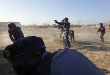 Police open fire on striking miners at the Lonmin Platinum Mine near Rustenburg, South Africa, Thursday, Aug. 16, 2012. South African police opened fire Thursday on a crowd of striking workers at a platinum mine, leaving an unknown number of people injured and possibly dead. Motionless bodies lay on the ground in pools of blood. (AP Photo)