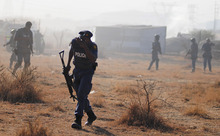 A policeman runs from teargas after police opened fire on striking miners at the Lonmin Platinum Mine near Rustenburg, South Africa, Thursday, Aug. 16, 2012. South African police opened fire Thursday on a crowd of striking workers at a platinum mine, leaving an unknown number of people injured and possibly dead. Motionless bodies lay on the ground in pools of blood. (AP Photo)