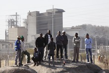 Bystanders watch as police, unseen, investigate the crime scene at the Lonmin Platinum mine, near Rustenburg, South Africa, Friday, Aug. 17, 2012, a day after several striking workers were shot and killed when police opened fire on striking mineworkers. (AP Photo/Denis Farrell)