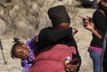 An unidentified woman carries a child on her back as she cries and wanders around near to the scene of a police shooting incident at the Lonmin Platinum mine, near Rustenburg, South Africa, Friday, Aug. 17, 2012.   The woman did not give her name, but is searching for her missing husband a day after several striking workers were shot and killed when police opened fire on striking mineworkers. (AP Photo/Denis Farrell)