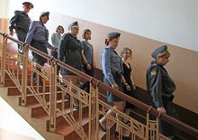 Nadezhda Tolokonnikova, center, Yekaterina Samutsevich, third left, and Maria Alekhina, second right, members of feminist punk group Pussy Riot are escorting by the police to a court in Moscow, Russia, Friday, Aug. 17, 2012. The three members who were jailed in March following a guerrilla performance denouncing President Vladimir Putin in Moscow's main cathedral have unwillingly emerged as vivid and very different characters. They await a verdict Friday on charges of hooliganism motivated by religious hatred. (AP Photo/Mikhail Metzel)