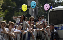 Supporters of feminist punk group Pussy Riot stand behind barricades surrounding a court, in Moscow, Russia on Friday, Aug 17, 2012.  Pussy Riot members, two of whom have young children, are charged with hooliganism connected to religious hatred, but the case is widely seen as a warning that authorities will only tolerate opposition under tightly controlled conditions.(AP Photo/Sergey Ponomarev)