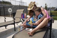 Kim Raff    The Salt Lake Tribune Asher Moody sits on his mother Amanda Moody's lap and eats a snack while taking a break from swimming in the Suncrest Community Pool in Draper, Utah on August 15, 2012. Asher's parents decided it would be best for him to start kindergarten at Summit Academy this month -- after he turned 6 on Aug. 1 -- rather than a year ago, when he'd barely turned 5 by the first day of school.