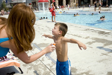 Kim Raff    The Salt Lake Tribune Amanda Moody sprays suntan lotion on her son, Asher Moody, before he swims at the Suncrest Community Pool in Draper, Utah on August 15, 2012. Asher's parents decided it would be best for him to start kindergarten at Summit Academy this month -- after he turned 6 on Aug. 1 -- rather than a year ago, when he'd barely turned 5 by the first day of school.