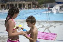 Kim Raff    The Salt Lake Tribune Asher Moody tastes his sister's snow cone while taking a break from swimming in the Suncrest Community Pool in Draper, Utah on August 15, 2012. Asher's parents decided it would be best for him to start kindergarten at Summit Academy this month -- after he turned 6 on Aug. 1 -- rather than a year ago, when he'd barely turned 5 by the first day of school.
