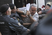 Police officers detain former world chess champion Garry Kasparov, a leading opposition activist, outside the court where a trial of the feminist punk group Pussy Riot is held, in Moscow, Friday, Aug. 17, 2012. A Moscow judge sentenced three members of the provocative punk band Pussy Riot to two years in prison each on hooliganism charges on Friday following a trial that has drawn international outrage as an emblem of Russia's intolerance of dissent. (AP Photo/Lisa Kessler)