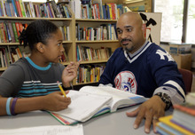 In this Aug. 7, 2012 photo, Phillip Covington, right, talks with his son Giovanni as he works on a mathematics lesson in the library of Todd Academy in Indianapolis. Struggling Indiana public school districts are buying billboard space, airing radio ads and even sending principals door-to-door in an unusual marketing campaign aimed at persuading parents not to move their children to private schools as the nation's largest voucher program doubles in size. The Indianapolis schools are underfunded and understaffed, Giovanni Covington's parents say, and the teachers