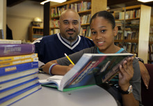 In this Aug. 7, 2012 photo, Phillip Covington, left, poses with his son Giovanni as he works on a mathematics lesson in the library of Todd Academy in Indianapolis. Struggling Indiana public school districts are buying billboard space, airing radio ads and even sending principals door-to-door in an unusual marketing campaign aimed at persuading parents not to move their children to private schools as the nation's largest voucher program doubles in size. The Indianapolis schools are underfunded and understaffed, Giovanni Covington's parents say, and the teachers