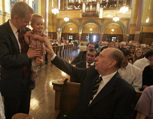 LDS Church President Thomas S. Monson visits with Scott Daw of Herriman and Daw's 1-year-old son, Brennan Daw. Jim Urquhart/The Salt Lake Tribune