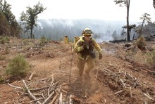 Firefighter Josh Gillick carries a hoses to water down a hot spot of the Ponderosa Fire near Viola, Calif., Monday, Aug. 20, 2012.   More than 1,400 fire fighters are battling the fire that has destroyed seven homes, burned 23 square miles. The fire that started Saturday is just 5 percent contained. (AP Photo/Rich Pedroncelli)
