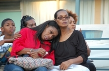 Anne Carter Winters, right, comforts her daughter, Teresa Carter, at a vigil for their grandson and son, Chavis Carter, in Memphis, Tenn., on Monday, Aug. 20, 2012. Chavis Carter, a man police say shot himself in the head while his hands were cuffed behind him in the back of an Arkansas patrol car, tested positive for methamphetamine, anti-anxiety medication and other drugs, according to an autopsy report released Monday that listed his death as a suicide. (AP Photo/Jeannie Nuss)