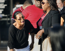 Anne Carter Winters breaks down into tears as she arrives to a Monday, Aug. 20, 2012 prayer vigil held on the grounds of The National Civil Rights Museum in Memphis, Tenn., for her grandson Chavis Carter, who Jonesboro, Ark., police say committed suicide while handcuffed. Winters is aided by Ursula Holmes, a lawyer with the Cochran law firm. (AP Photo/The Commercial Appeal, Stan Carroll)