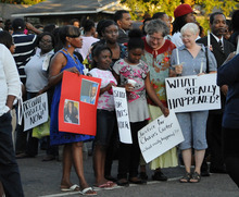 FILE - In this Aug. 6, 2012 file photo, supporters of Chavis Carter and his family, including 9-year-olds Taelor Chavis, center left, and Kimi Miller, center right, hold signs during the candlelight vigil held in honor of Carter at the First Baptist Church in Jonesboro, Ark. Carter was shot in the head while his hands were cuffed behind him in an Arkansas patrol car on July 28. An autopsy report released Monday, Aug. 20, lists Carter's death as a suicide. (AP Photo/The Jonesboro Sun, Krystin McClellan, File)