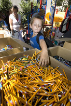 Paul Fraughton | Salt Lake Tribune Skyler Coulten-Slaten, age 7, reaches into a large box filled with pencils as he  fills his bag with school supplies. He was one  of the 150 school aged children living at  The Road Home Shelter who received  back to school  items  thanks to the Apple Tree Program, a four week campaign by the shelter to collect new clothing and school supplies. Apple Trees with paper apples attached, featuring specific children's needs, were set up at various business in the area and participants  bought  items for their chosen  child.  Monday, August 20, 2012